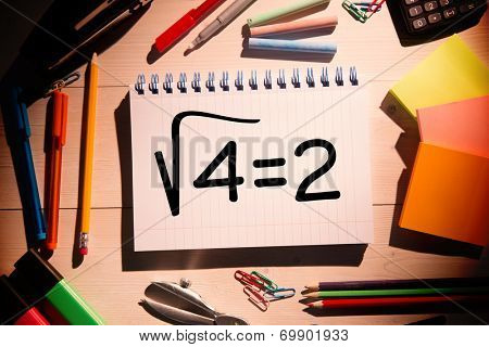 Square root of four on notepad against students desk