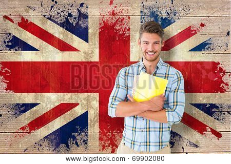 Young student smiling against union jack flag in grunge effect
