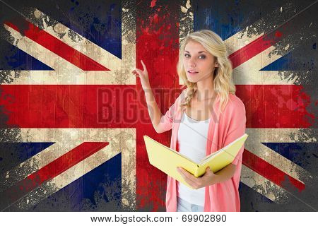 Young pretty student pointing and reading against union jack flag in grunge effect