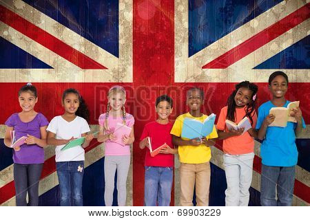 Elementary pupils reading books against union jack flag in grunge effect