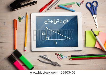 Composite image of digital tablet on students desk showing math equations