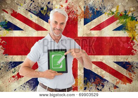 Mature student showing tablet pc against grunge union jack flag