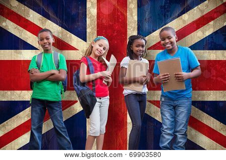Cute pupils smiling at camera against union jack flag in grunge effect
