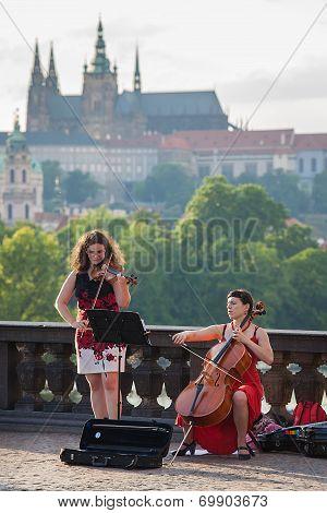 Street musicians perform with Prague Castel on background
