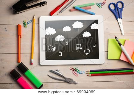 Composite image of digital tablet on students desk showing cloud computing doodle