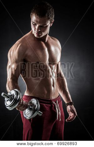 Handsome athletic man pumping up muscles with dumbbells