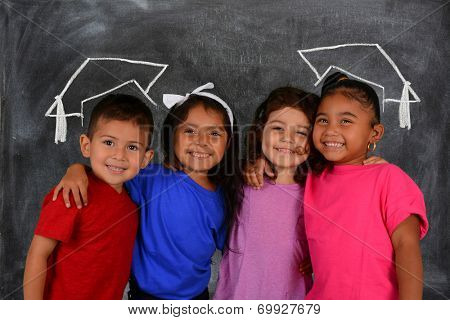 Young children at school standing at the chalkboard