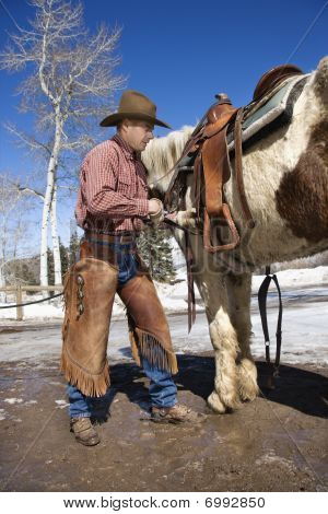 Cowboy Putting Saddle On Horse