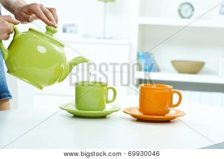Pouring water from tea kettle to mug high key bright background, table, pastel colors, close up, indoors home.
