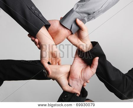 Close up of ring of hands isolated on background. Symbolic, teamwork, cooperation, ties, business team, working together.