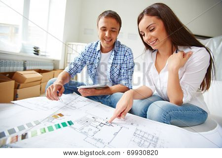 Portrait of young couple sitting in their new flat and discussing its plan