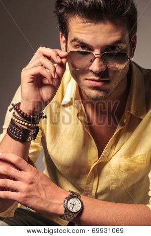 cool fashion model taking off his sunglasses and looks to the camera