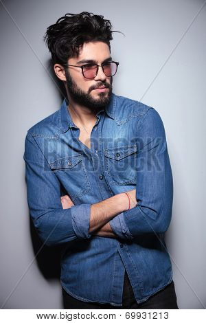 fashion man in jeans clothes standing with hands crossed and looks away from the camera