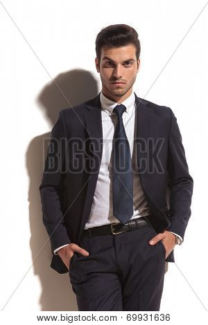 cool fashion business man standing with hands in pockets against white wall