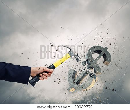 Close up of businessman hand crashing dollar sign with hammer