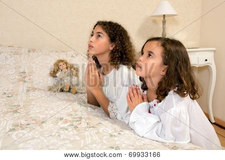 Adorable victorian girls kneeling in their vintage bedroom and praying