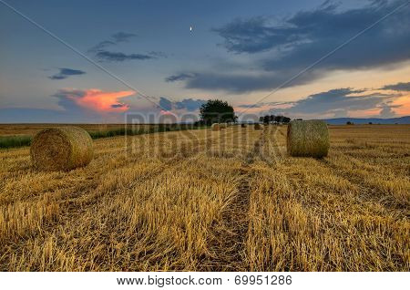 clouds over field with hay