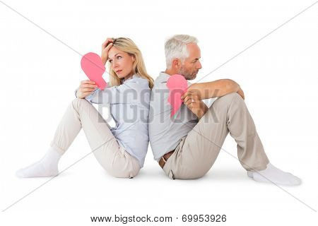 Unhappy couple sitting holding two halves of broken heart on white background