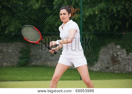 Pretty tennis player playing on court on a sunny day