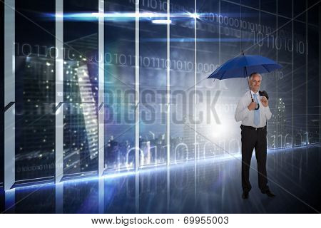 Happy businessman holding umbrella against hologram interface in office overlooking city