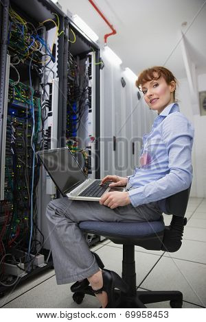 Happy technician sitting on swivel chair using laptop to diagnose servers in large data center