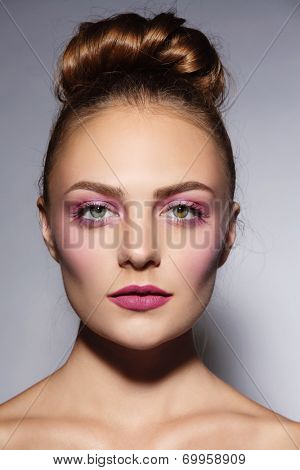 Young beautiful girl with stylish pink make-up and hair bun