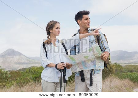 Hiking young couple with map pointing ahead on mountain terrain