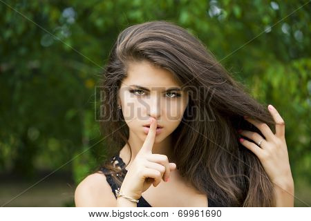Young beautiful brunette woman has put forefinger to lips as sign of silence, against green summer garden