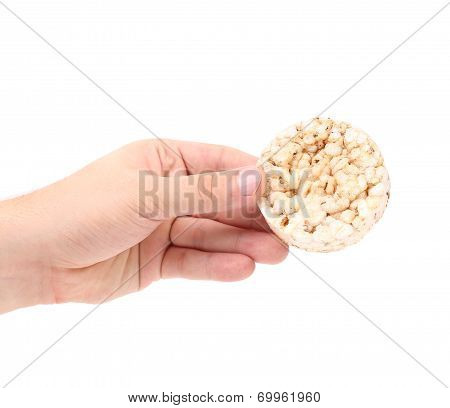 Puffed rice snack in hand.