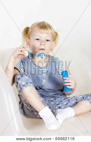 little girl playing with a bubbles maker