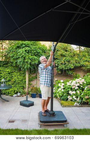 Senior Man Setting Up Beach Parasol