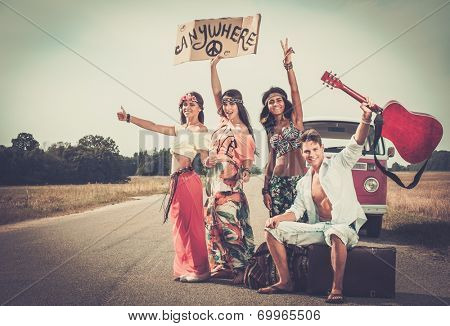 Multi-ethnic hippie hitchhikers with guitar and luggage on a road