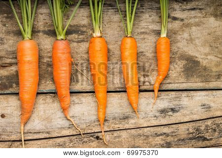 Fresh Ripe Carrots Lying On Wooden Background. Vitamins On The Table.