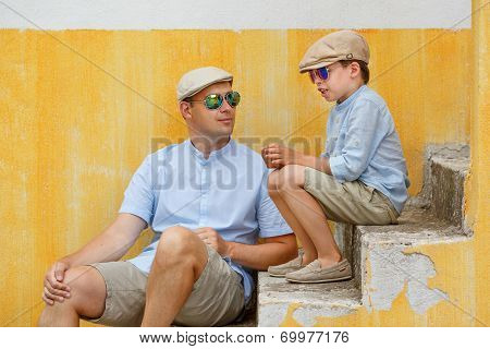 Happy father and son talking and having rest outdoors in city