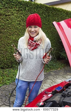 a young woman takes off her car with jumper cables. jump start in the winter on cold days