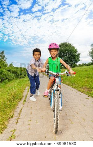 Boy helps girl to ride bike and holds handle-bar