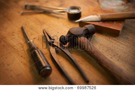 Old workshop. Old and well used hammer, pliers and screw driver with warm lighting.