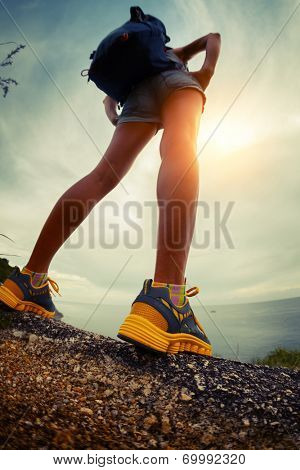 Lady hiker standing on the rocky ground. Focus on the boot