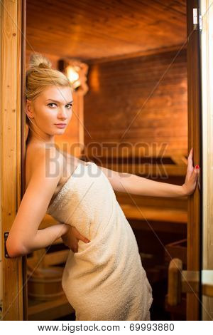 Young woman relaxing in a sauna, taking a break from her busy schedule, taking care of herself, enjoying the wellness benefits her job provides