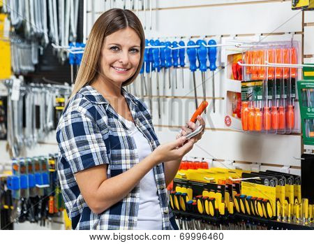 Portrait of female customer holding cellphone and screwdriver in hardware store