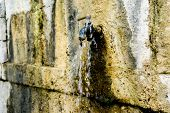 foto of bib tap  - Old rusty water tap in a village - JPG
