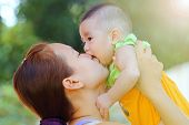 stock photo of kiddie  - Mother kissing her baby close up - JPG