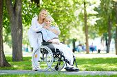 stock photo of take responsibility  - Pretty nurse taking care of senior patient in a wheelchair - JPG