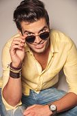 picture of take off clothes  - fashion man looks up and takes off his sunglasses - JPG