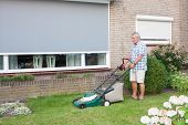 image of grass-cutter  - Dutch senior with serious look and mowing his front yard grass with an electric mower as spare time activity after retirement - JPG