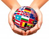stock photo of longitude  - Flags of the world in globe and hands - JPG