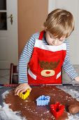 stock photo of ginger bread  - 3 years child baking ginger bread cookies for Christmas in home - JPG