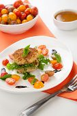 stock photo of crab-cakes  - Close up of crab cakes and cherry tomato salad appetizer garnished with basil and balsamic vinegar sauce.