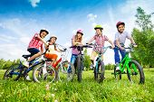 Постер, плакат: Children in colorful helmets hold their bikes