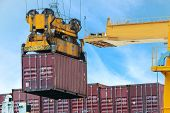 stock photo of loading dock  - Container Cargo freight ship with working crane loading bridge in dock - JPG